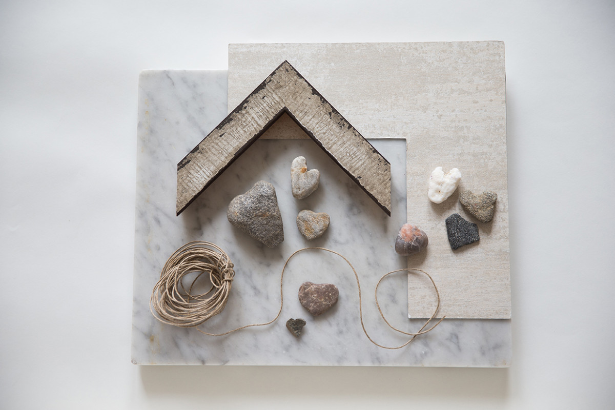 Process Photo of a Narrative Framed Piece Composed of Heart Shaped Rocks